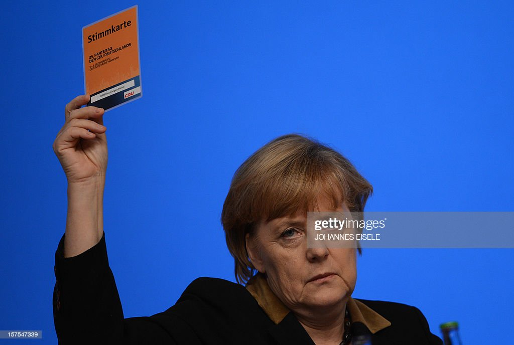 German Chancellor Angela Merkel holds up her voting card for a vote on putting gay couples on the same tax footing as heterosexual married ones during a congress of Germany's ruling conservative Christian Democratic Union (CDU) party on December 4, 2012 in Hanover, central Germany. German Chancellor Angela Merkel was re-elected head of her conservative Christian Democrats (CDU) by more than 97 percent of delegates' votes at a two-day party congress. It was Merkel's best result since she took over as chairman of the CDU in 2000 and comes as she gears up for fighting for a third term at the helm of Europe's top economy in elections expected in September 2013.