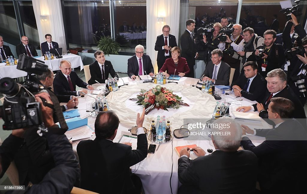 German Chancellor Angela Merkel (back, C) hosts Russian President Vladimir Putin (L), French President Francois Hollande (foreground, C) and Ukrainian President Petro Poroshenko (R) during talks for peace in eastern Ukraine at the chancellery on October 19, 2016 in Berlin. Merkel said the talks, the first four-way summit for a year, were aimed at 'offering a brutally honest assessment' of progress on implementing the frayed Minsk peace accords for Ukraine. / AFP / dpa Pool / Michael Kappeler