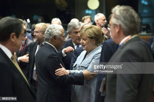 German Chancellor Angela Merkel hug Portugal's Prime minister Antonio Costa in Brussels on October 19 2017 during the summit of European Union...