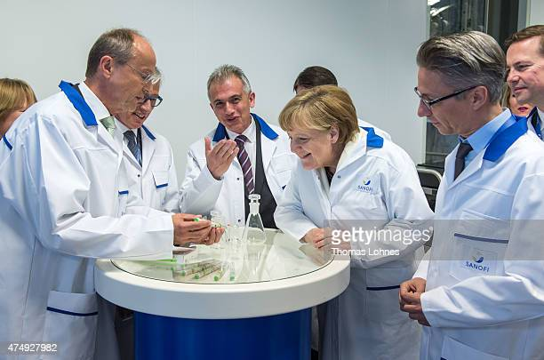 German Chancellor Angela Merkel inspects an insulin pen as she visits the new production facility for sterile glass vials at the Sanofi...