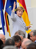 German Chancellor Angela Merkel invites guests to joint her in the garden during the annual meeting of foreign diplomatic representatives at Meseberg...
