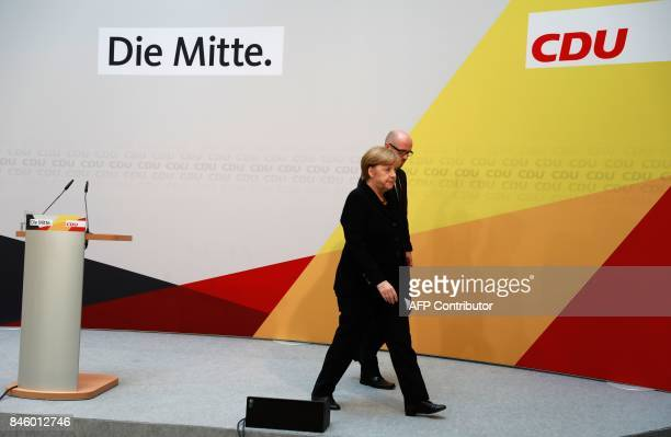 German Chancellor Angela Merkel is accompanied by CDU secretary general Peter Tauber as she leaves after giving a statement on September 12 2017 in...