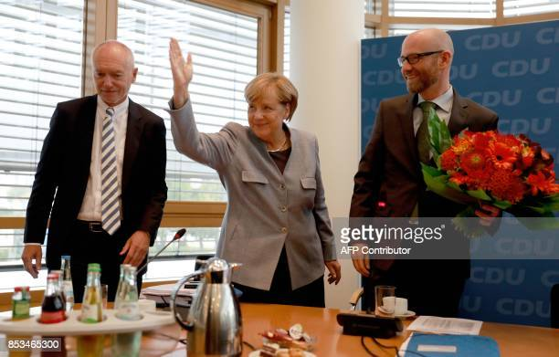 German Chancellor Angela Merkel is flanked by the secretary general of her conservative Christian Democratic Union party Peter Tauber and party...