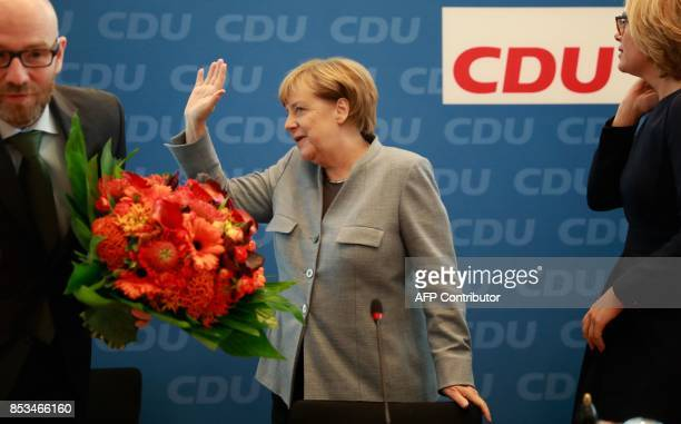German Chancellor Angela Merkel is flanked by the secretary general of her conservative Christian Democratic Union party Peter Tauber and one of five...