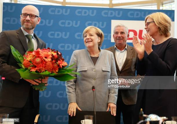 German Chancellor Angela Merkel is flanked by the secretary general of her conservative Christian Democratic Union party Peter Tauber and two of five...
