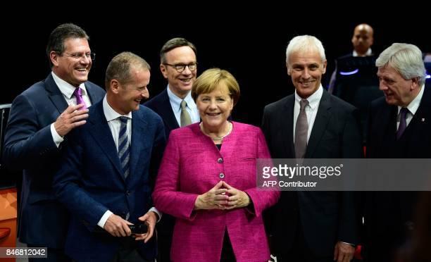German Chancellor Angela Merkel is flanked by Volkswagen chairman Matthias Mueller and Volkswagen board member Herbert Diess as she visits the booth...