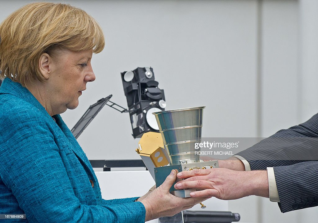 German Chancellor Angela Merkel is given an Autonomous Star Sensor, a flight proven sensor autonomous star tracking system for long-term GEO and LEO missions for telecommunication, science and Earth observation satellites during a visit at the Jena-Optronik GmbH (Ltd) on May 2 , 2013 in Jena, eastern Germany. AFP PHOTO / ROBERT MICHAEL