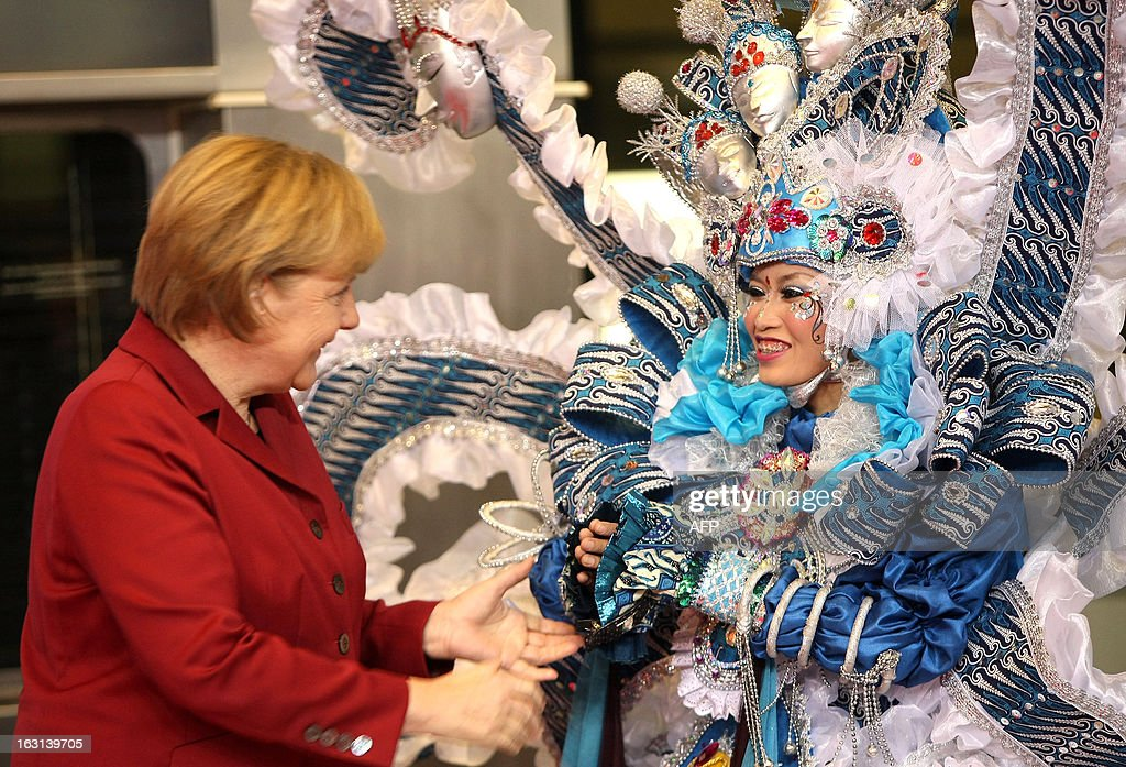German Chancellor Angela Merkel (L) is greeted by an Indonesian hostess at the ITB Berlin tourism convention (Internationale Tourismus-Boerse) prior to its opening in Berlin on March 5, 2013. The ITB Berlin runs from March 6-10 and features Indonesia as its partner country for the event in 2013.