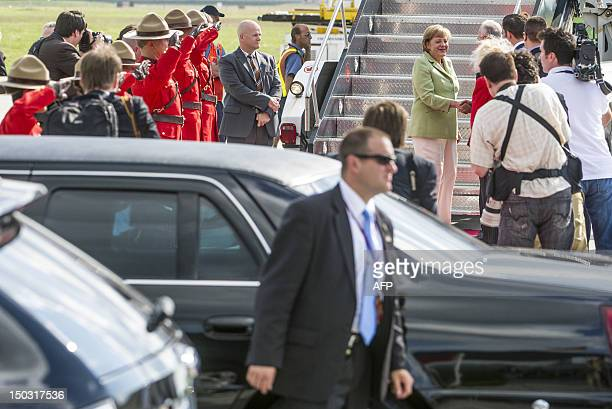 German Chancellor Angela Merkel is greeted by officials as she arrives at the MacdonaldCartier International Airport in Ottawa Ontario Canada Merkel...