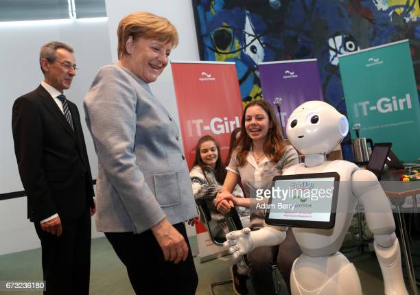 German Chancellor Angela Merkel is introduced to Pepper the Robot by participant Lilly Antonia on Girls' Day on April 26 2017 in Berlin Germany The...