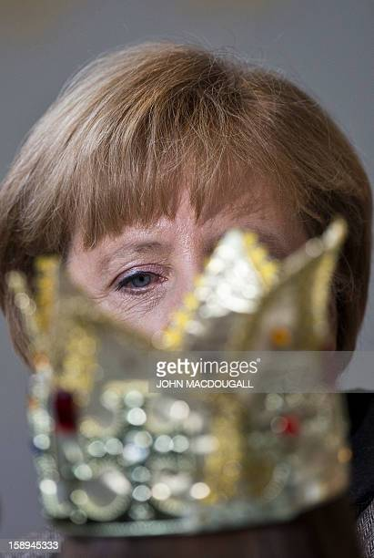 German Chancellor Angela Merkel is obscured by a young Carol singer's paper crown at the Chancellery in Berlin on January 4 2013 Carol singers...