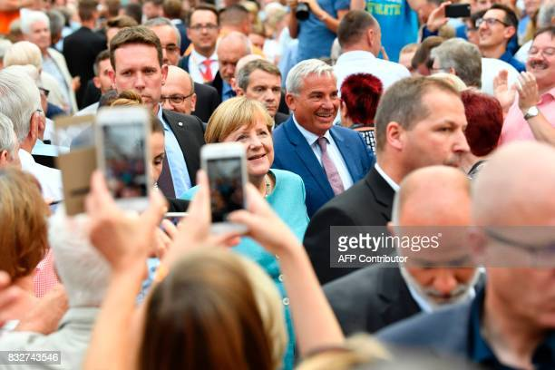 German Chancellor Angela Merkel is photographed by supporters as she arrives to address an election campaign rally of the Christian Democratic Union...