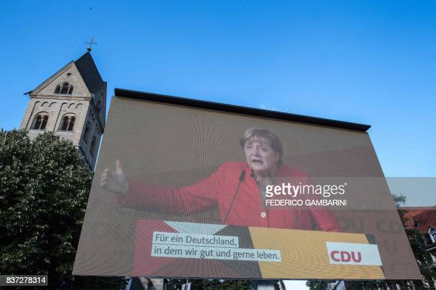 German Chancellor Angela Merkel is seen on a screen addressing an election campaign rally of the Christian Democratic Union in Bergisch Gladbach...