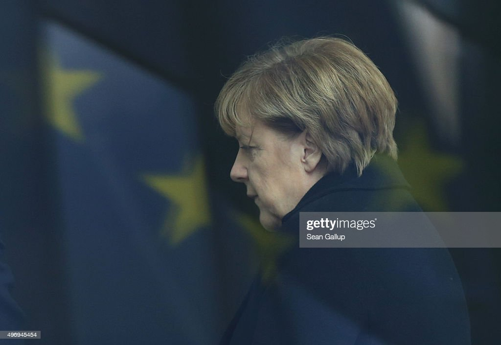 German Chancellor Angela Merkel is seen through a window and the reflection of a flag of the European Union as she waits for the arrival of...