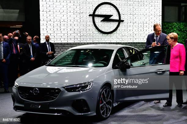 German Chancellor Angela Merkel is shown an Opel car by Michael Lohscheller CEO of Opel as they visit the booth of Opel during the official opening...