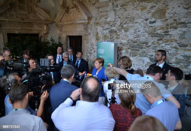German Chancellor Angela Merkel is surrounded by journalists as she gives a statement during the Summit of the Heads of State and of Government of...