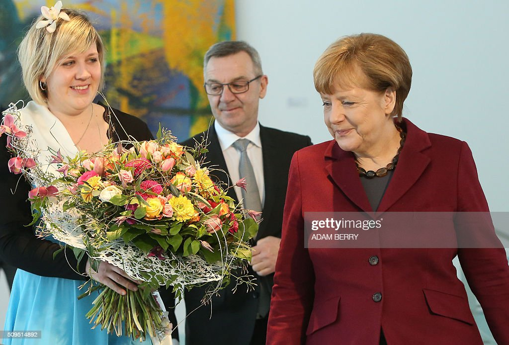 German Chancellor Angela Merkel (R) is to receive a Valentine's Day bouquet from a Gardener's Association at the Chancellery in Berlin on February 11, 2016. / AFP / Adam BERRY