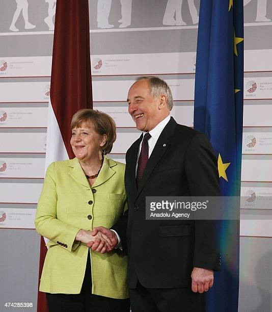 German Chancellor Angela Merkel is welcomed by Latvian President Andris Berzins as she arrives at the House of the Blackhead for a dinner at the...