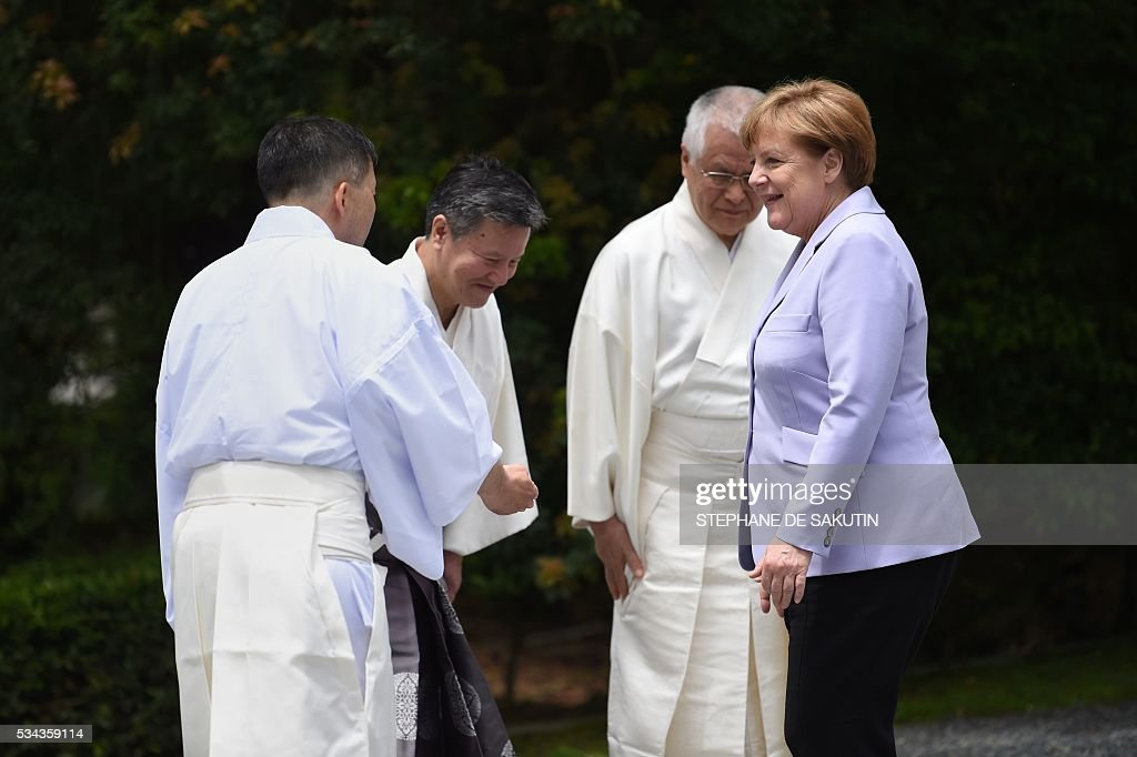 German Chancellor Angela Merkel (R) is welcomed by Shinto priests as she arrives at Ise-Jingu Shrine in the city of Ise in Mie prefecture, on May 26, 2016, on the first day of the G7 leaders summit. World leaders kick off two days of G7 talks in Japan on May 26 with the creaky global economy, terrorism, refugees, China's controversial maritime claims, and a possible Brexit headlining their packed agenda. / AFP / STEPHANE