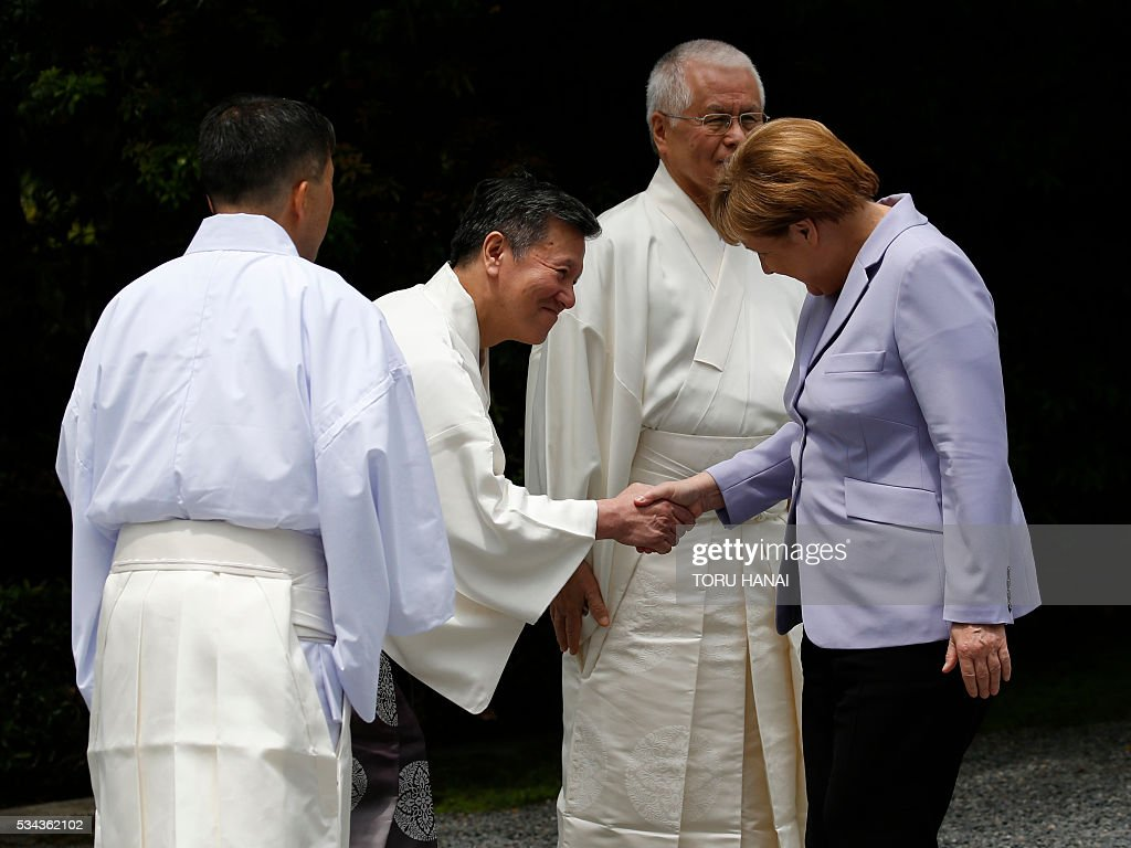 German Chancellor Angela Merkel (R) is welcomed by Shinto priests as she visits Ise-Jingu Shrine in the city of Ise in Mie prefecture, on May 26, 2016, on the first day of the G7 leaders summit. World leaders kick off two days of G7 talks in Japan on May 26 with the creaky global economy, terrorism, refugees, China's controversial maritime claims, and a possible Brexit headlining their packed agenda. / AFP / POOL / TORU