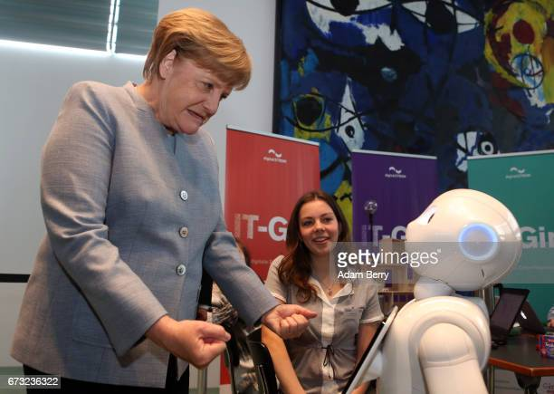 German Chancellor Angela Merkel jokingly displays clenched fists as Pepper the Robot declines an offer to shake her hand when introduced to the...