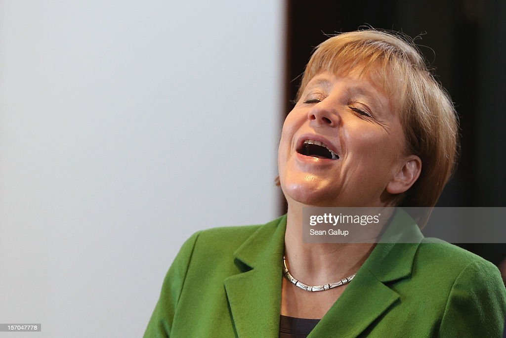 German Chancellor Angela Merkel laughs at a colleagues comment as she arrive for the wekkly German government cabinet meeting on November 28, 2012 in Berlin, Germany. High on the morning's agenda was changes to the country's pension system.