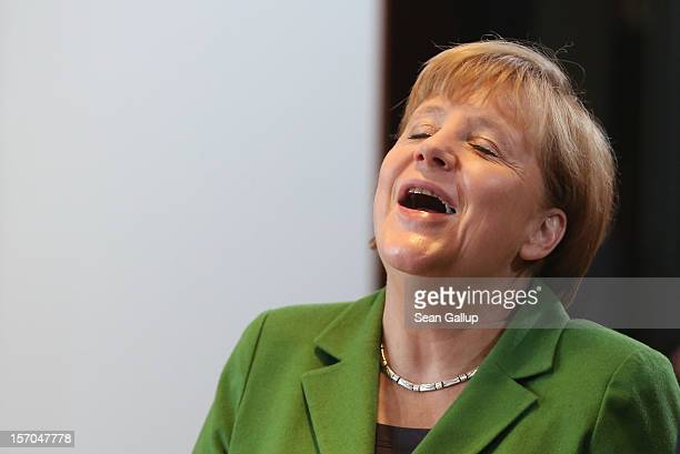 German Chancellor Angela Merkel laughs at a colleagues comment as she arrive for the wekkly German government cabinet meeting on November 28 2012 in...