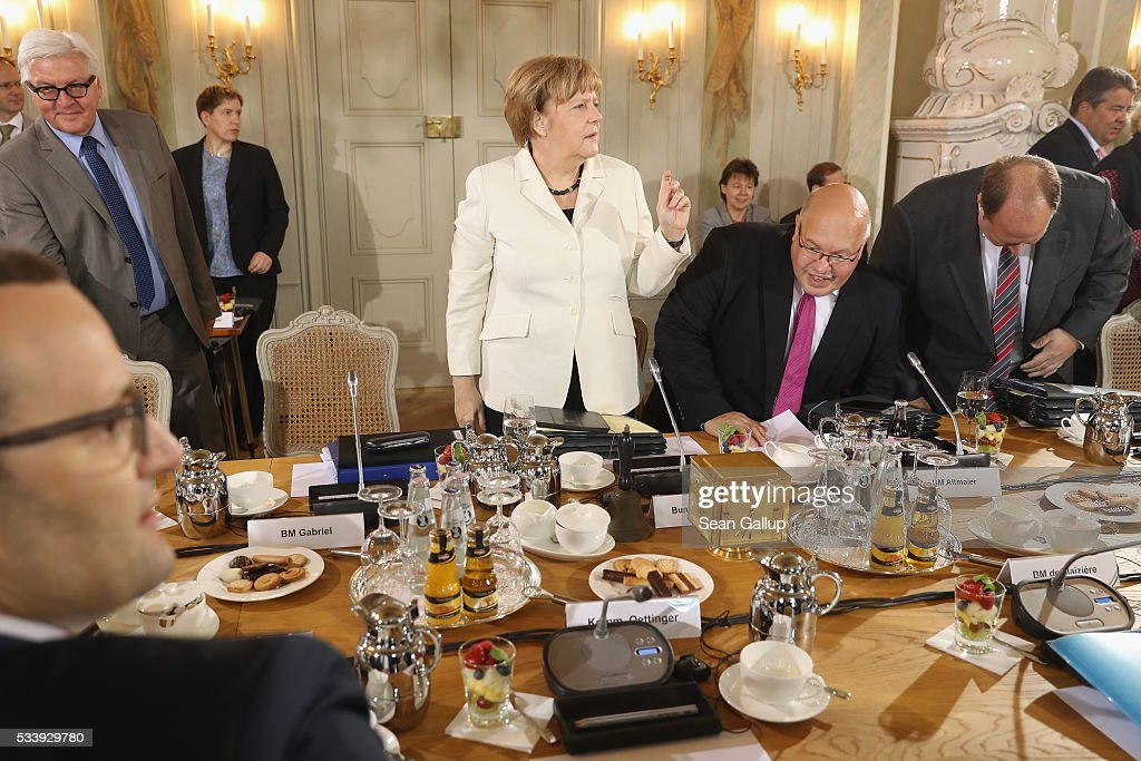 German Chancellor Angela Merkel (C) leads a meeting of the German government cabinet together with European Commissioner for Digital Economy and Society Guenther Oettinger at Schloss Meseberg palace on May 24, 2016 in Gransee, Germany. The government cabinet is meeting at Schloss Meseberg for a two-day retreat.