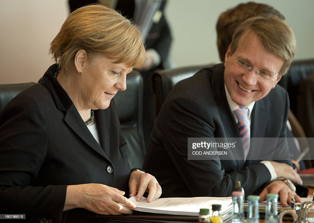 German Chancellor Angela Merkel leads the weekly cabinet meeting seated next to her chief of staff Roland Pofalla at the Chancellery in Berlin on February 6, 2013. Germany's education minister and a close ally of Chancellor Angela Merkel was fighting for her political life Wednesday after having her doctorate revoked for plagiarism. AFP PHOTO / ODD ANDERSEN