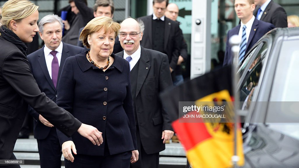 German Chancellor Angela Merkel (3rd L) leaves after the opening of the exhibition 'Berlin 1933 On the Path to Dictatorship', tracing Adolf Hitler's rise to power in Germany in 1933 to mark 80 years since he became chancellor, on January 30, 2013 at the open-air documentation center Topographie des Terrors in Berlin. The exhibition located at the former headquarters of the Gestapo, the secret police of the Nazi regime, traces Hitler's first months in power through photos, newspapers and posters. AFP PHOTO / JOHN MACDOUGALL