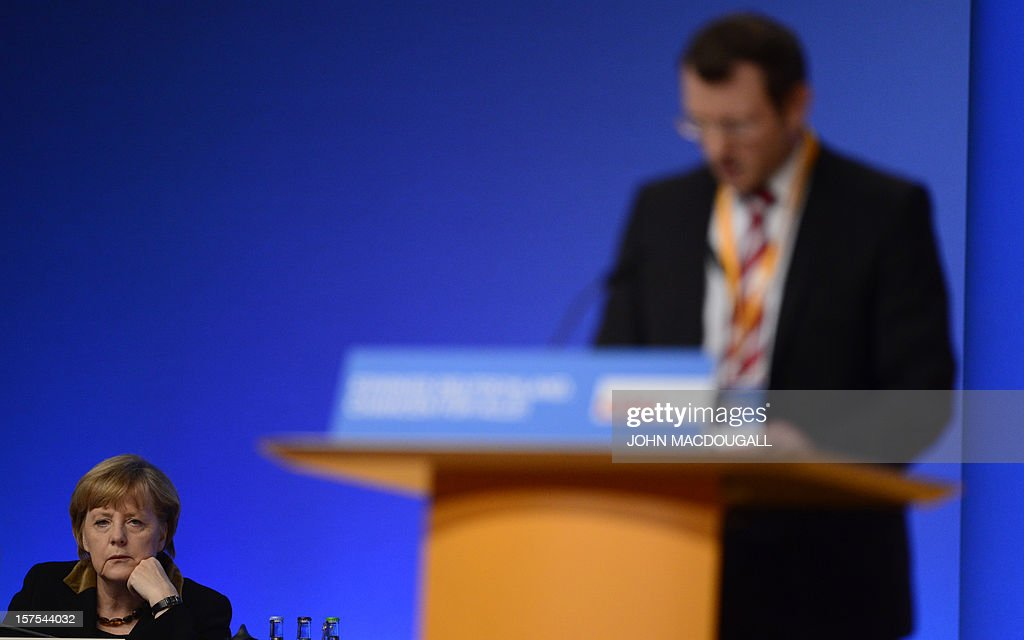 German Chancellor Angela Merkel listens as CDU party member Jan-Marco Luczak speaks during a congress of Germany's ruling conservative Christian Democratic Union (CDU) party on December 4, 2012 in Hanover, central Germany. German Chancellor Angela Merkel was re-elected head of her conservative Christian Democrats (CDU) by more than 97 percent of delegates' votes at a two-day party congress. It was Merkel's best result since she took over as chairman of the CDU in 2000 and comes as she gears up for fighting for a third term at the helm of Europe's top economy in elections expected in September 2013.