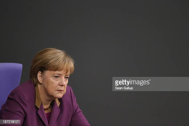 German Chancellor Angela Merkel listens to debates over a financial aid package for stricken Greece at the Bundestag on November 30 2012 in Berlin...