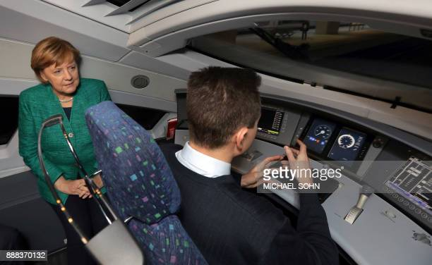 German Chancellor Angela Merkel listens to driver Martin Spiegelhauer as she attends a part of the opening passage of a special ICE railway route...
