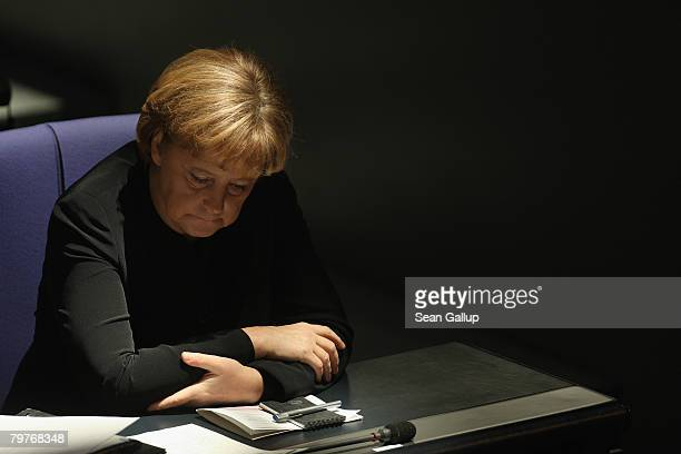 German Chancellor Angela Merkel listens to Finance Minister Peer Steinbrueck address the Bundestag in a government statement on the current state of...
