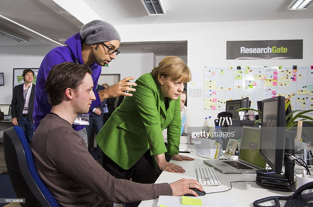 German Chancellor Angela Merkel listens to manager Ijad Madisch (C) during her visit of the company Research Gate on March 7, 2013 in Berlin, Germany. Chancellor Merkel and Economy Minister Philipp Roesler visited young internet companies and talked to financiers.