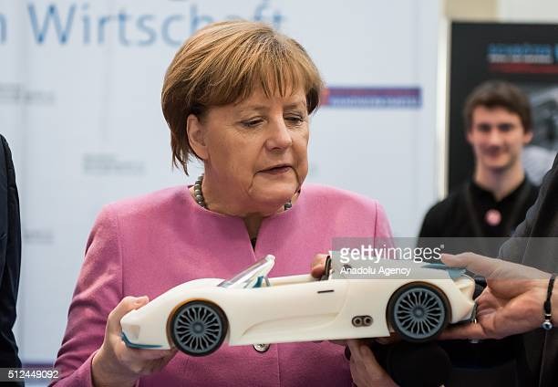 German Chancellor Angela Merkel looks at a 3D printed car during a meeting of German Economic Associations at International Trade Fair in Munich...