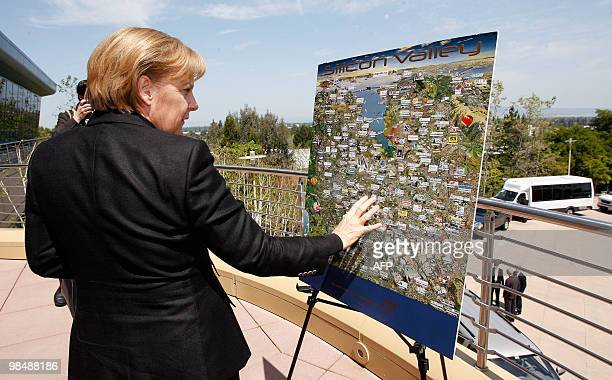 German Chancellor Angela Merkel looks at a map of Silicon Valley during her visitt to SAP Company in Palo Alto California 15 April 2010 Chancellor...