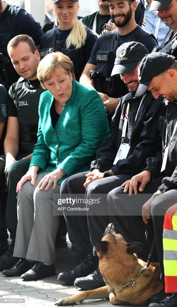 German Chancellor Angela Merkel (C) looks at a police dog as she poses with policemen who were deployed during the G20 summit in Hamburg, northern Germany, on July 8, 2017. / AFP PHOTO / POOL / Patrik STOLLARZ