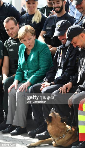 German Chancellor Angela Merkel looks at a police dog as she poses with policemen who were deployed during the G20 summit in Hamburg northern Germany...