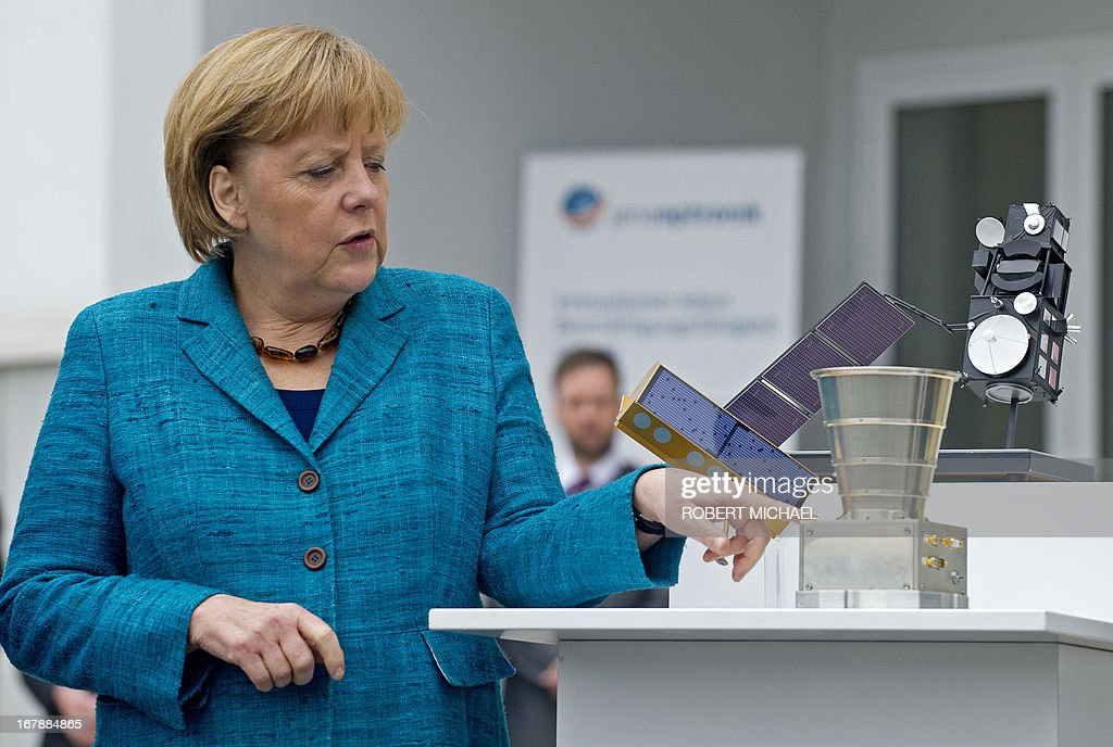 German Chancellor Angela Merkel looks at an Autonomous Star Sensor, a flight proven sensor autonomous star tracking system for long-term GEO and LEO missions for telecommunication, science and Earth observation satellites during a visit at the Jena-Optronik GmbH (Ltd) on May 2 , 2013 in Jena, eastern Germany. AFP PHOTO / ROBERT MICHAEL