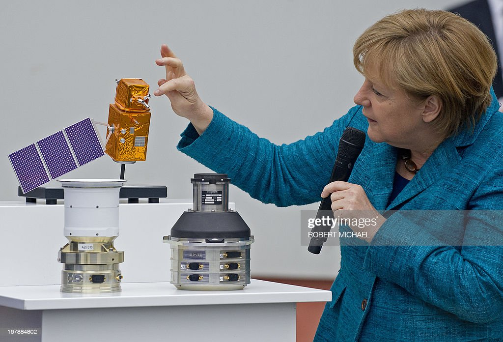 German Chancellor Angela Merkel looks at flight proven sensor autonomous star tracking system for long-term GEO and LEO missions for telecommunication, science and Earth observation satellites during a visit at the Jena-Optronik GmbH (Ltd) on May 2 , 2013 in Jena, eastern Germany.