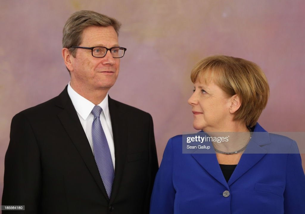 German Chancellor Angela Merkel looks at Foreign Minister <a gi-track='captionPersonalityLinkClicked' href=/galleries/search?phrase=Guido+Westerwelle&family=editorial&specificpeople=208748 ng-click='$event.stopPropagation()'>Guido Westerwelle</a>, who is a member of the German Free Democrats (FDP), after he received his dismissal certificate from German President Joachim Gauck at a ceremony for the outgoing German government at Bellevue Palace on October 22, 2013 in Berlin, Germany. The ministers will stay on in their functions until a new government is formed, which will most likely be a coalition between the German Christian Democrats (CDU) and the German Social Democrats (SPD). For the FDP members the ceremony today is especially poignant, as the party failed in recent German elections to receive the 5% minimum of votes necessary to retain its seats in the Bundestag, which means the party no longer has political say on the federal level.