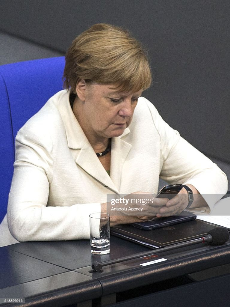 German Chancellor Angela Merkel looks at her phone during a meeting on the results of the United Kingdom's EU Referendum at the German Federal Parliament (Bundestag) in Berlin, Germany on June 28, 2016.