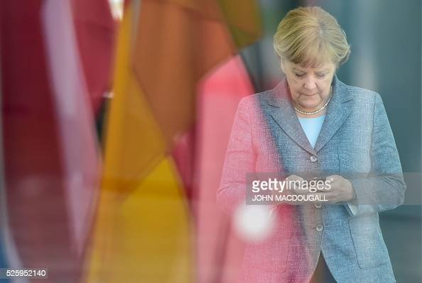German chancellor Angela Merkel looks at her smartphone while waiting at the chancellery for the arrival of the Latvian Prime Minister in Berlin on...