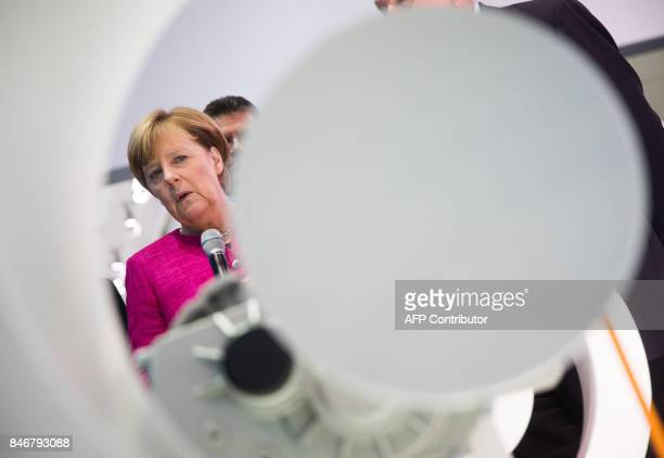 German Chancellor Angela Merkel looks at the system of an electric drive as she visits the booth of Bosch at the Internationale Automobil Ausstellung...