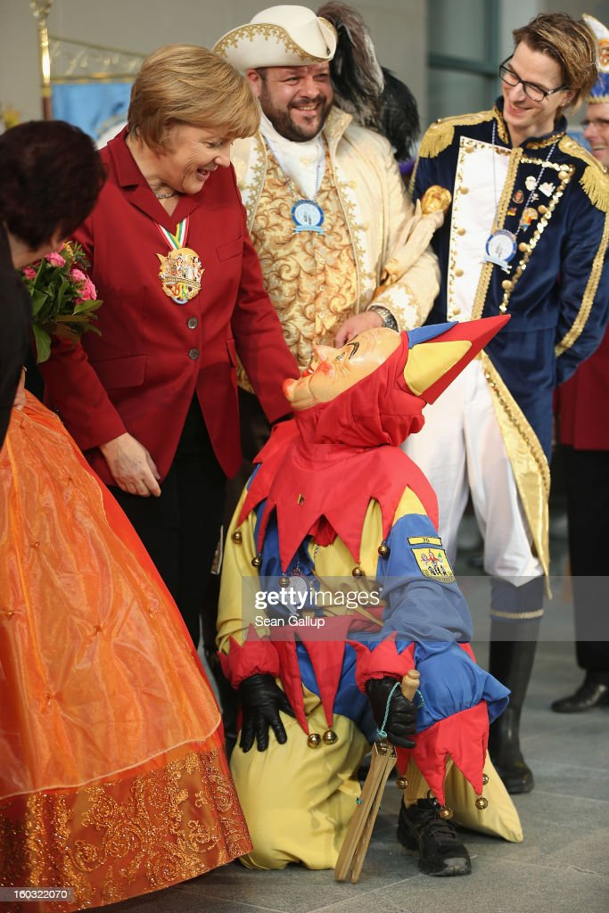 German Chancellor <a gi-track='captionPersonalityLinkClicked' href=/galleries/search?phrase=Angela+Merkel&family=editorial&specificpeople=202161 ng-click='$event.stopPropagation()'>Angela Merkel</a> looks down at a masked Carnival fool while meeting with Carnival delegates from all over Germany on January 29, 2013 in Berlin, Germany. Merkel received the delegates at an annual ceremony at the Chancellery. Germany is in the midst of Carnival season, which ends with its highpoint between Rose Monday and Ash Wednesday in a tradition common in several countries in Europe and the Americas.
