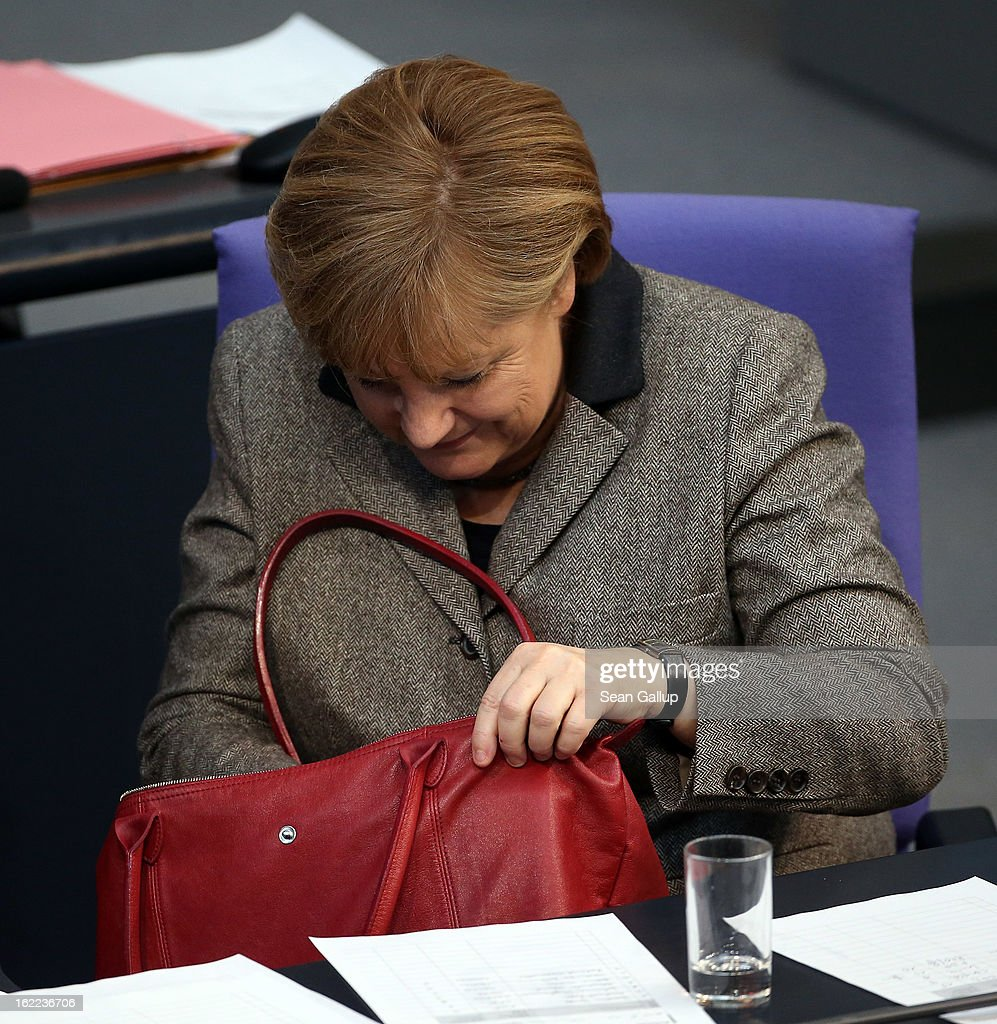 German Chancellor <a gi-track='captionPersonalityLinkClicked' href=/galleries/search?phrase=Angela+Merkel&family=editorial&specificpeople=202161 ng-click='$event.stopPropagation()'>Angela Merkel</a> looks in her handbag after giving a government declaration on the forthcoming European Union budget that was agreed upon at a summit in Brussels recently on February 21, 2013 in Berlin, Germany. The budget required wrangling and compromises and will give more money to economically-stricken member state.