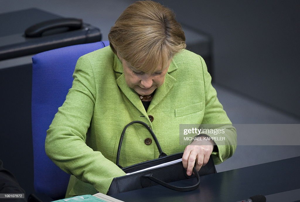 German Chancellor Angela Merkel looks into her handbag as she attends a debate at the Bundestag, the lower house of parliament, on May 21, 2010 in Berlin. The German parliament is set to unblock its share of a trillion-dollar rescue package for debt-stricken eurozone countries , after Chancellor Angela Merkel warned the euro was 'in danger'.