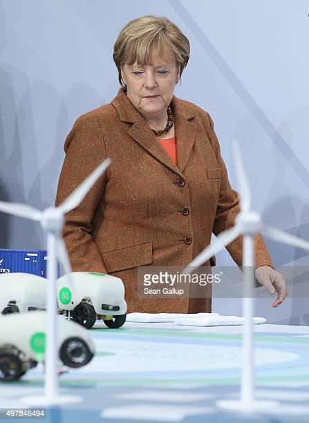 German Chancellor Angela Merkel looks modelsof cars and wind turbines at a presentation of 5G technology for traffic at the 2015 IT Summit on...