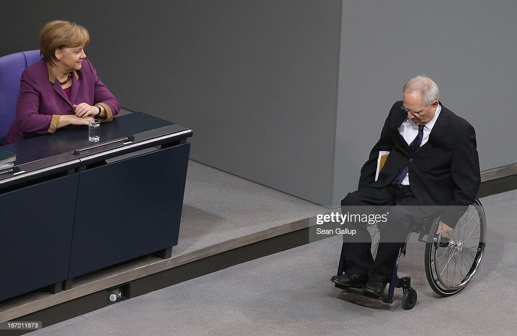 German Chancellor <a gi-track='captionPersonalityLinkClicked' href=/galleries/search?phrase=Angela+Merkel&family=editorial&specificpeople=202161 ng-click='$event.stopPropagation()'>Angela Merkel</a> looks on as Finance Minister Wolfgang Schaeuble finished speaking during debates over a financial aid package for stricken Greece at the Bundestag on November 30, 2012 in Berlin, Germany. The Bundestag was expected to later approve the measure that will allow the next tranche of financial assistance for Greece.
